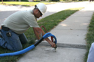 Technician raising sidewalk with PolyLevel®